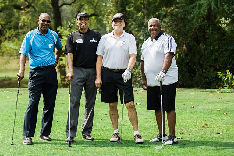 Four people stand together at a golf outing.