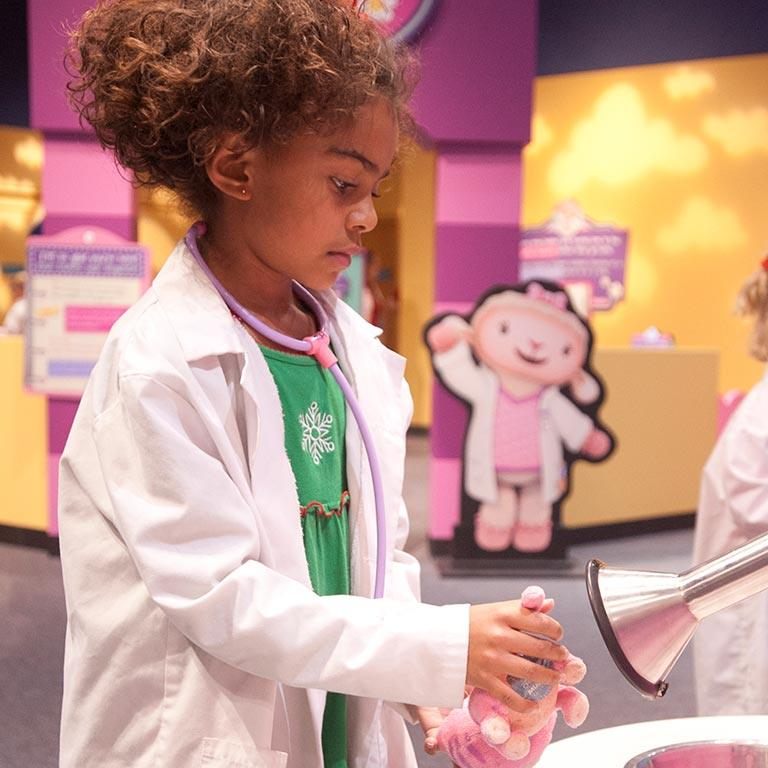 A little girl pretends to be a doctor.